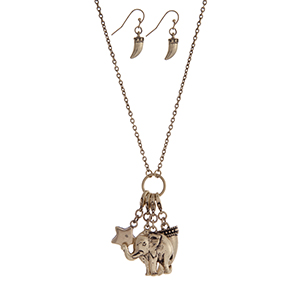 "Burnished gold tone necklace set with a charm cluster pendant featuring elephant, horn, star and flower charms. Approximately 30"" in length."