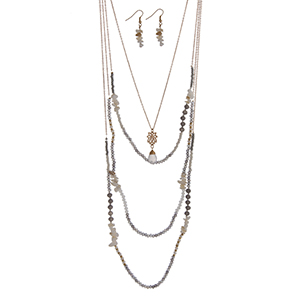 "Gold tone multi-layer necklace set with gray and white seed beads, glass beads and a flower pendant. Approximately 36"" in length."