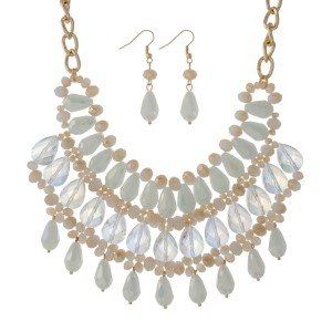 "Gold tone bib necklace set with ivory, white and champagne colored beads. Approximately 18"" in length."