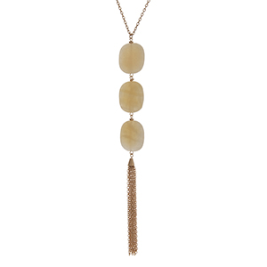 "Gold tone necklace with three beige square natural stones and a metal tassel. Approximately 36"" in length."