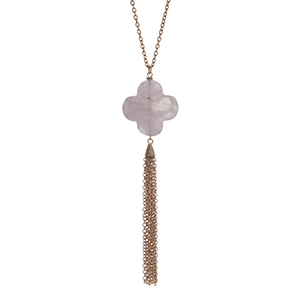 """Gold tone necklace with a rose quartz natural stone quatrefoil pendant and metal tassel. Approximately 36"""" in length."""