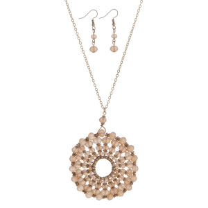 """Gold tone necklace set with a peach beaded circle pendant. Approximately 32"""" in length."""