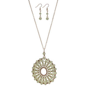 "Gold tone necklace set with a mint green beaded circle pendant. Approximately 32"" in length."