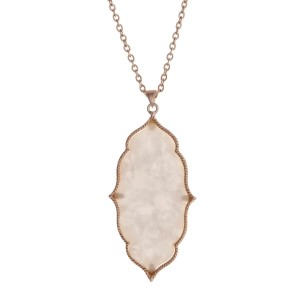 "Gold tone necklace with a Moroccan shaped pearlized ivory pendant. Approximately 36"" in length."