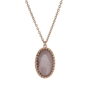 "Gold tone necklace with a faceted gray oval pendant. Approximately 32"" in length."