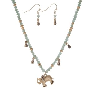 "Gold tone necklace set with gray beads and an elephant pendant. Approximately 18"" in length."