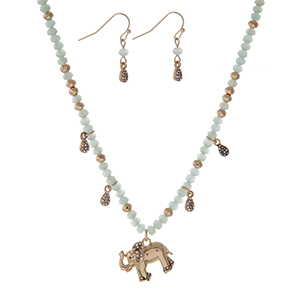 "Gold tone necklace with light blue faceted beads and an elephant pendant. Approximately 18"" in length."