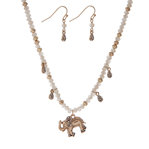 "Gold tone necklace with white faceted beads and an elephant pendant. Approximately 18"" in length."