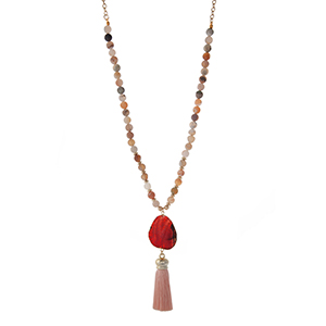 "Gold tone necklace displaying botswana natural stone beads and a peach fabric tassel. Approximately 32"" in length."