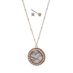 """Gold tone necklace with a howlite pendant accented with pave rhinestones. Approximately 24"""" in length."""
