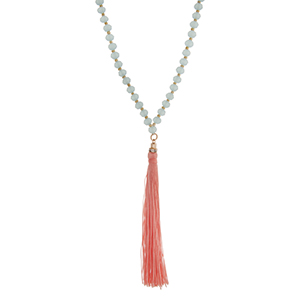 "Light blue beaded necklace with a peach fabric tassel. Approximately 36"" in length."