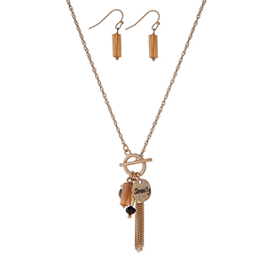 "Gold tone necklace set displaying tassel, tigers eye stone, and ""serenity"" stamped circle charms. Approximately 18"" in length."