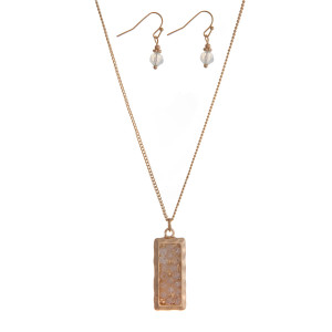 "Dainty gold tone necklace set with a rectangle pendant and clear beads. Approximately 16"" in length."