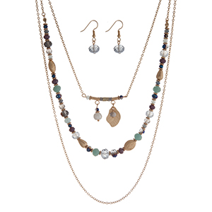 "Gold tone triple row necklace set with purple, mint green, and navy blue beads and a feather charm. Approximately 24"" in length."