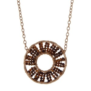 "Gold tone necklace displaying a brown beaded circle pendant. Approximately 32"" in length."