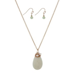 "Gold tone necklace set with a pale lime green wire wrapped natural stone teardrop pendant and matching earrings. Approximately 24"" in length."