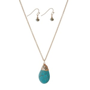 "Gold tone necklace set with a turquoise wire wrapped natural stone teardrop pendant and matching earrings. Approximately 24"" in length."