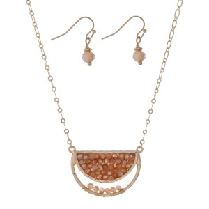 "Gold tone necklace set with a half circle shape and peach beads. Approximately 16"" in length."