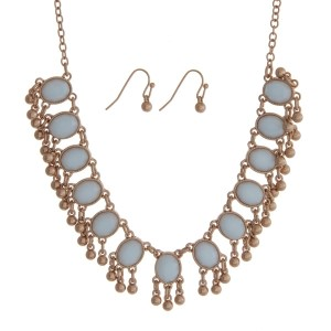 "Gold tone necklace set with light blue oval stones and matching fishhook earrings. Approximately 18"" in length."