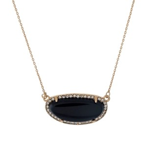 "Gold tone necklace with a black stone surrounded by clear rhinestones. Approximately 18"" in length."