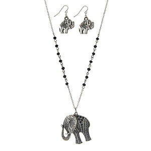 "Silver tone necklace set with black beads and an elephant pendant. Approximately 32"" in length."