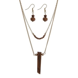 "Gold tone double layer necklace set with brown beads and a natural stone pendant. Approximately 22"" in length."