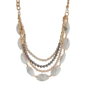 "Gold tone triple layer necklace with gray and pink beads and white stones. Approximately 16"" in length."