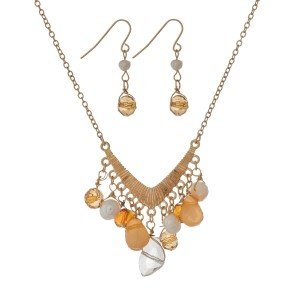 "Gold tone necklace set with a 'v' shaped pendant and peach bead charms. Approximately 18"" in length."