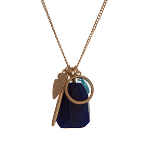 "Gold tone necklace with assorted charms and a faceted navy blue stone. Approximately 32"" in length."