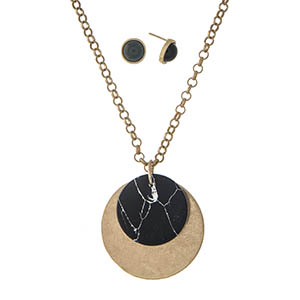 "Gold tone necklace set with a black circle pendant and matching stud earrings. Approximately 22"" in length."