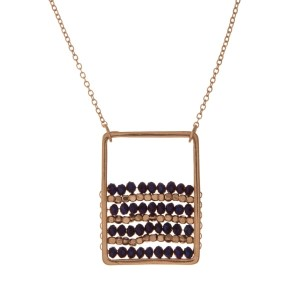 """Gold tone necklace with a purple beaded square pendant. Approximately 32"""" in length."""