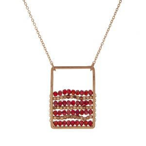 "Gold tone necklace with a burgundy beaded square pendant. Approximately 32"" in length."