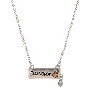 "Dainty silver tone necklace with a bar stamped with ""Survivor"" and a clear rhinestone charm. Approximately 16"" in length."
