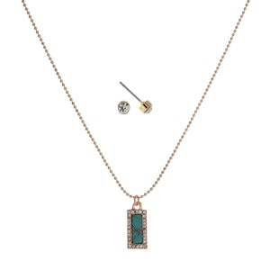 "Dainty gold tone necklace set with a turquoise stone pendant. Approximately 16"" in length."
