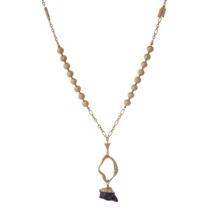 "Gold tone necklace with a hammered open pendant and a purple natural stone. Approximately 32"" in length."