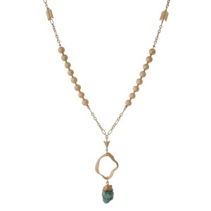 "Gold tone necklace with a hammered open pendant and a green natural stone. Approximately 32"" in length."
