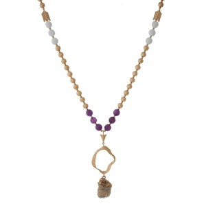 "Gold tone necklace with a hammered open pendant, purple beads, and an ivory natural stone. Approximately 32"" in length."