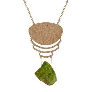"Gold tone necklace with a hammered pendant and a green natural stone. Approximately 32"" in length."