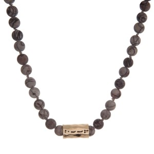 "Matte gray picture jasper beaded necklace with a hammered gold tone cylinder. Approximately 18"" in length."