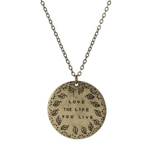 "Burnished gold tone necklace displaying a circle pendant stamped with ""Love the life you live."" Approximately 16"" in length."