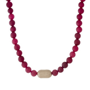 "Burgundy beaded necklace with a hammered gold tone nugget. Approximately 16"" in length."