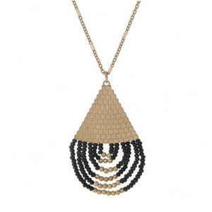 "Gold tone necklace with a half black beaded teardrop pendant. Approximately 32"" in length."