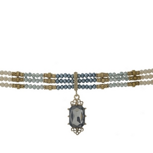 """Gold tone choker with navy, gray and iridescent green beads and a faceted gray stone focal. Approximately 12"""" in length."""