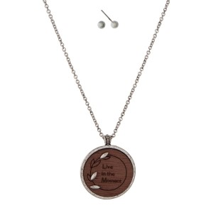 "Silver tone necklace set with a laser cut wooden pendant with ""Live in the Moment"" and matching stud earrings. Approximately 18"" in length."