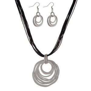 """Black multi cord necklace set with a hammered, matte silver tone circle pendant and matching fishhook earrings. Approximately 16"""" in length."""