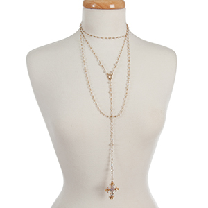 "Gold tone and clear iridescent beaded, layered 'Y' necklace with a cross pendant. Approximately 16"" in length."