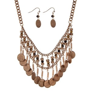 "Burnished gold tone necklace set with black beads and hanging decorative disk. Approximately 17"" in length."