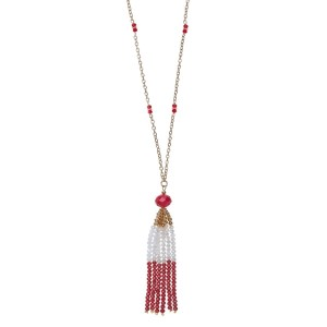 "Gold tone necklace with a crimson and white beaded tassel pendant. Approximately 32"" in length."