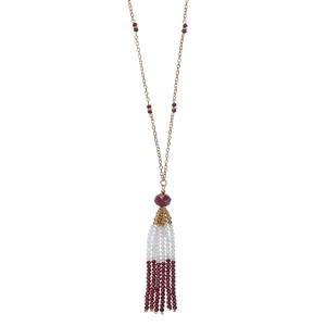 "Gold tone necklace with a maroon and white beaded tassel pendant. Approximately 32"" in length."