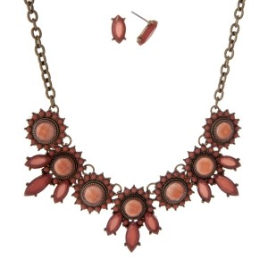 "Burnished gold tone necklace set with mauve circle and oval stones. Approximately 16"" in length."